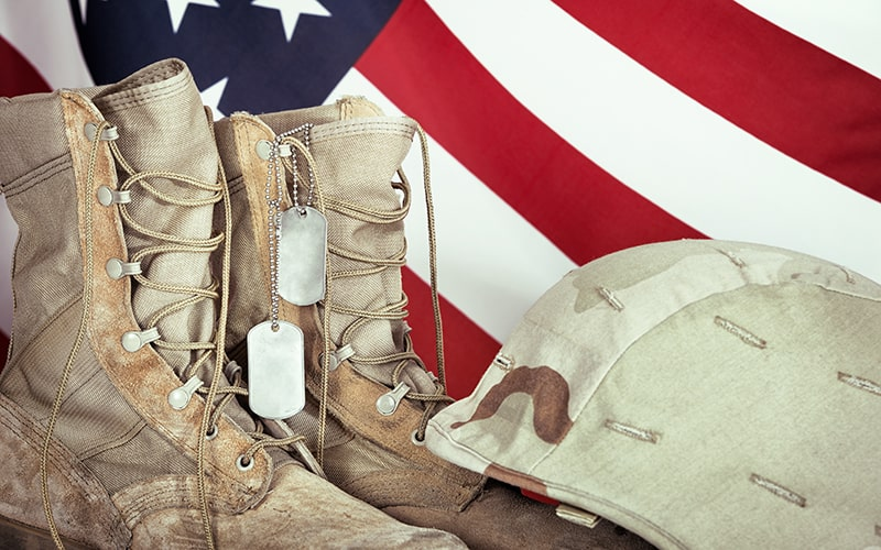 Combat boots, dog tags, and helmet in front of flag